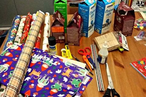 Πολύχρωμα χριστουγεννιάτικα χαρτιά, μια σακούλα πλαστική με ξωτικά και αυτοκόλλητο καπλαντίσματος ντουλαπιών.